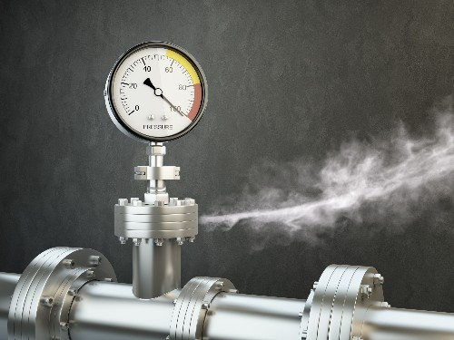 A pipe has a test gauge on top with a needle in the read zone while gas leaks from the pipe.